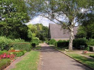 Blick auf Seitenfront des Friedhofsgebäudes mit Baum im Vordergrund und Gräber links