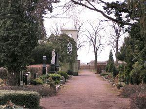 Weg mit Blick aufs Eingangstor links und rechts Gräber