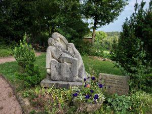 Grab mit Steinskultpur der trauernden Maria mit Jesus auf dem Schoß