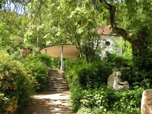 Pavillon und Steinengel in Mitten von Bäumen und Blättern